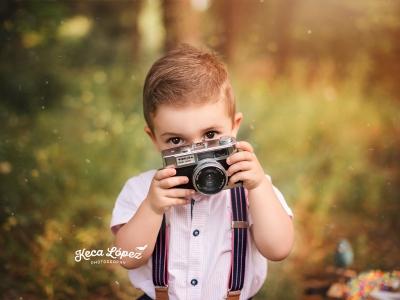 Niño con cámara en la mano, tirantes y camisa. Está en un bosque otoñal