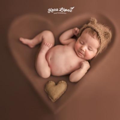 Bebé dentro de un corazón de color marrón con gorrito de osito. También hay un peluche en forma de corazón