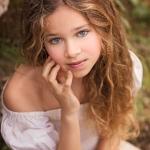 Niña con ojos azules mira a la cámara. Su pelo es rubio. Lleva un vestido blanco y está sentada en la tierra y se puede ver el musgo. Una imagen muy otoñal y bonita