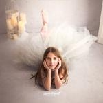 Bailarina en el suelo, su cabeza reposa sobre sus manos. Su vestido es de tull de color gris y el escenario es blanco.