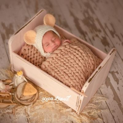 Recién nacido con gorrito de ratón dentro de una camita pequeñita y tapado con una manta trenzada. A su lado hay dos ratoncitos sentados en unas sillas comiendo queso