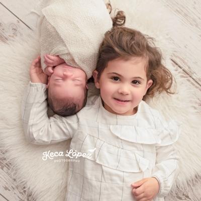 Hermana con hermano recién nacido. Niña con vestido blanco. Está sonriendo mientras abraza a su bebé