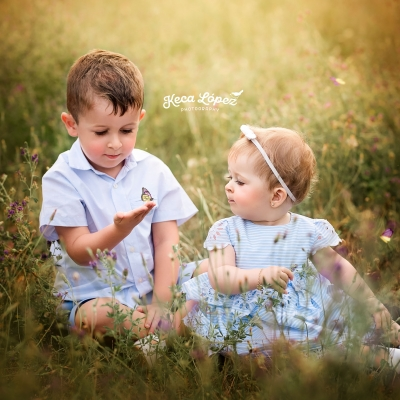 Fotografia hermanos en el campo. Niño con una mariposa