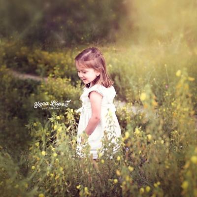 Niña en un campo verde con flores amarillas. Vestido blanco