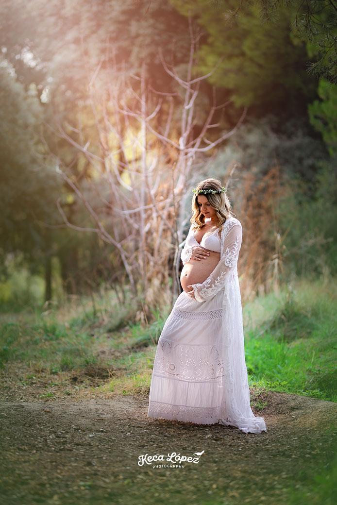 Mujer embarazada en el bosque con vestido blanco
